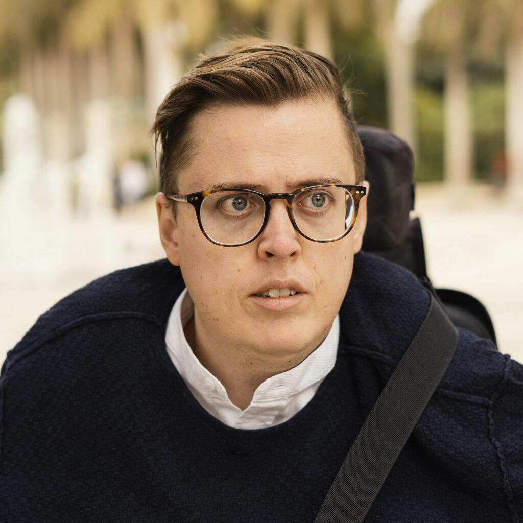 Portrætfoto: Rasmus kigger lidt forbi kameraet. Han bærer briller og en mørkeblå trøje over en hvid skjorte. I baggrunden ses slørede træer i varme farver.